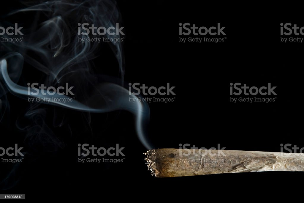 Lit Marijuana joint with smoke and black background stock photo