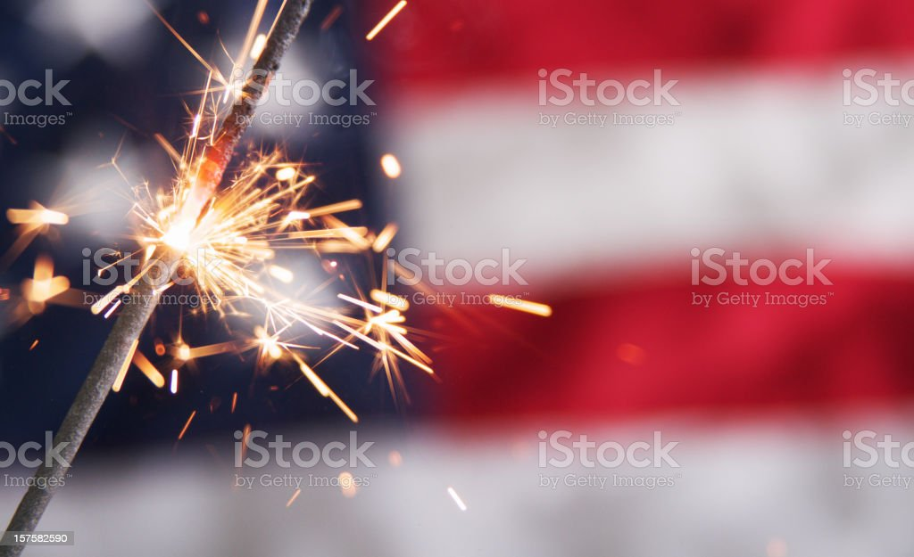Lit sparkler against a blurred American flag stock photo