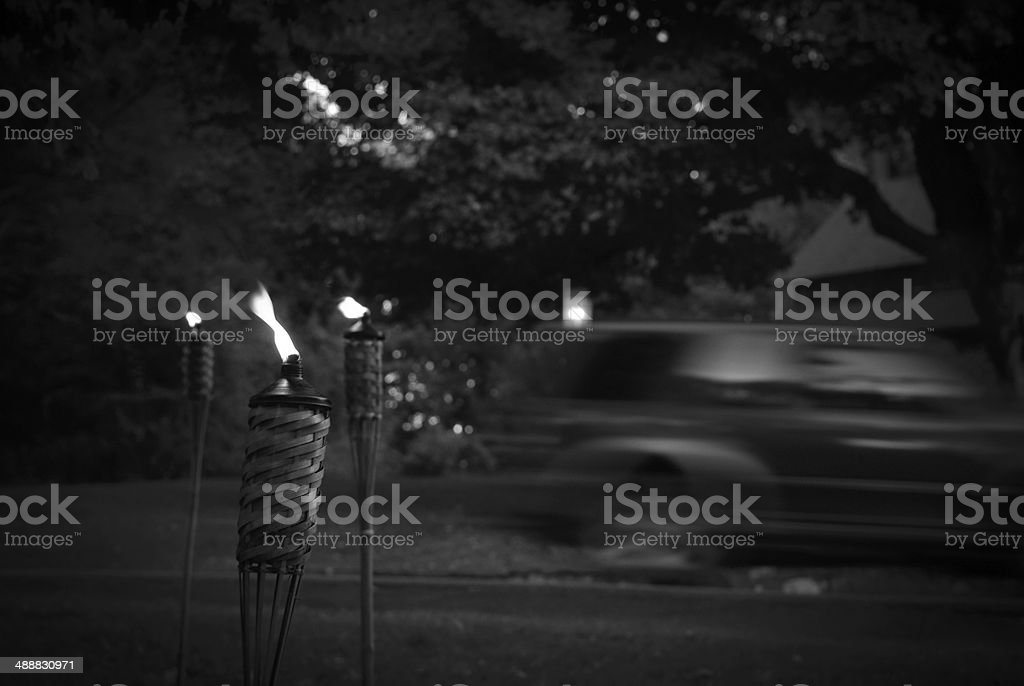 Lit Torches with a Passing Car stock photo