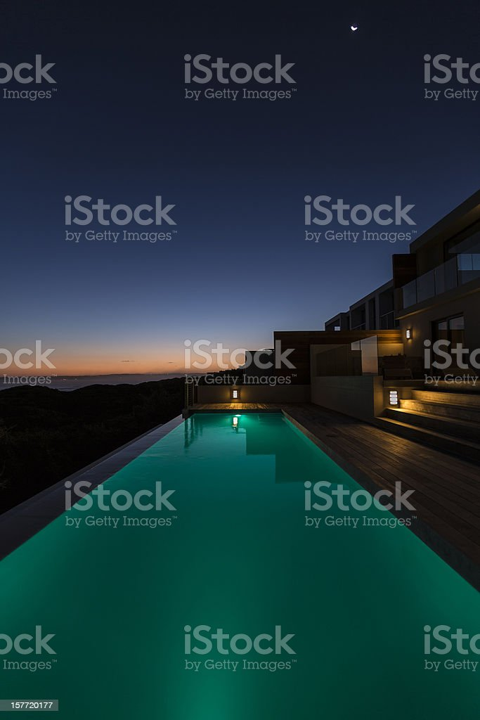 Lit up in ground pool in luxury villa at dusk royalty-free stock photo