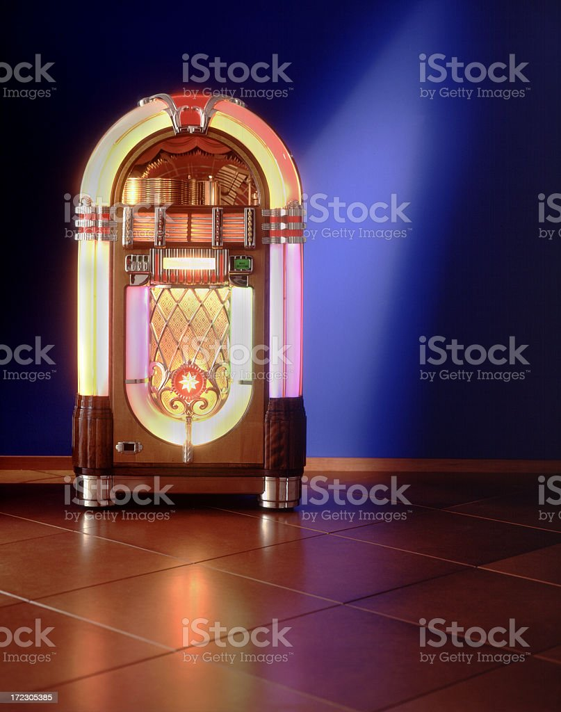 Lit up jukebox against a blue wall stock photo