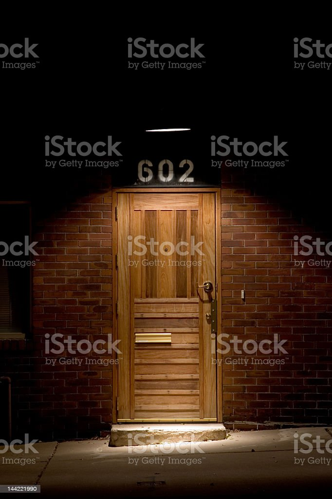 Lit up single wooden door. 602 royalty-free stock photo