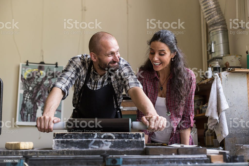 Lithograph workers using printing roller together stock photo