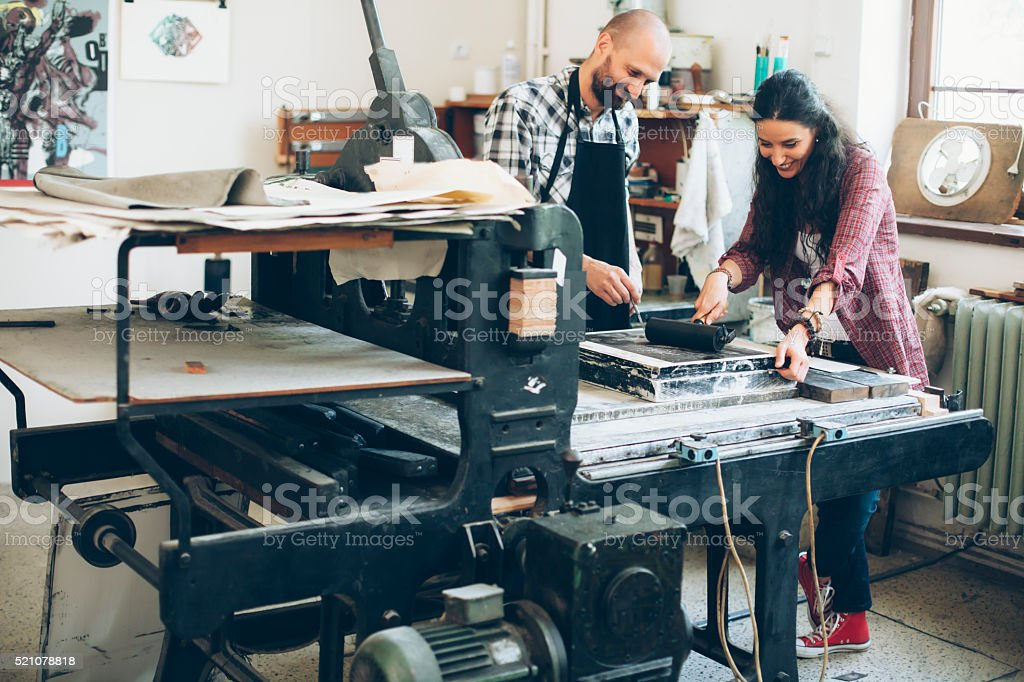 Lithography workers using rollers and printing press stock photo