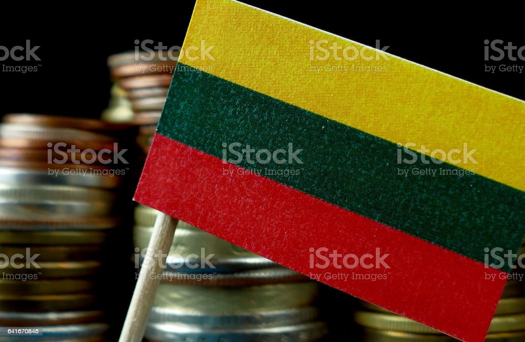 Lithuania flag waving with stack of money coins macro stock photo