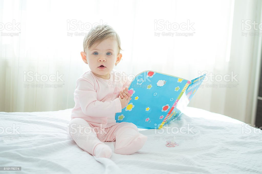 Litle innocent baby reading book on bed stock photo
