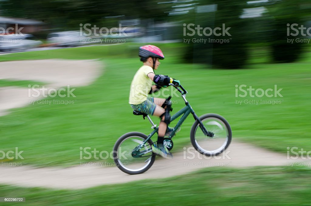 Litlle boy riding his bike in dirt road stock photo