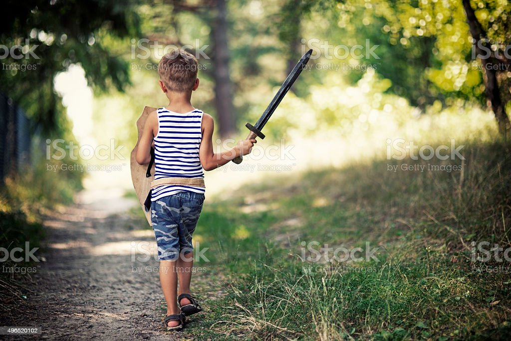 Litte boy playing knight walking on forest path stock photo