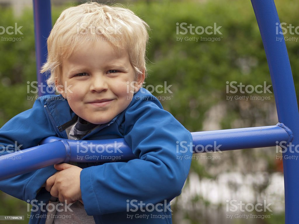 Litte caucasian boy smiling off climbing frame at playground royalty-free stock photo