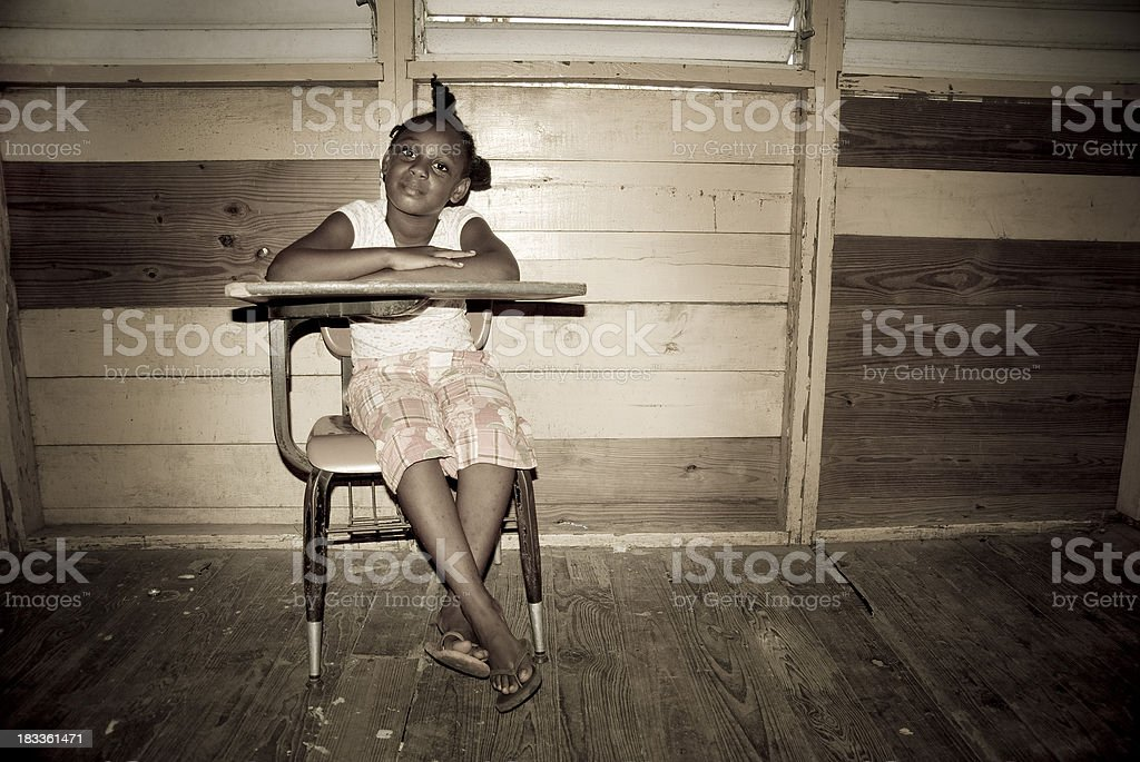 litte girl at desk ready to learn in abandoned classroom royalty-free stock photo