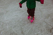 litte girl learning to skate on ice in winter