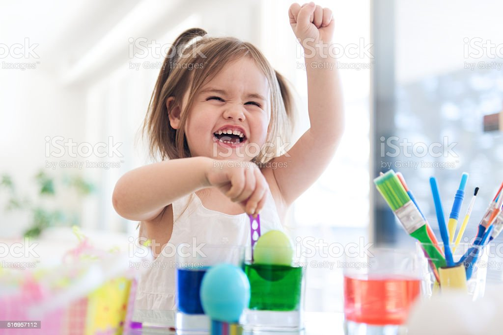 Litte girl painting easter eggs stock photo