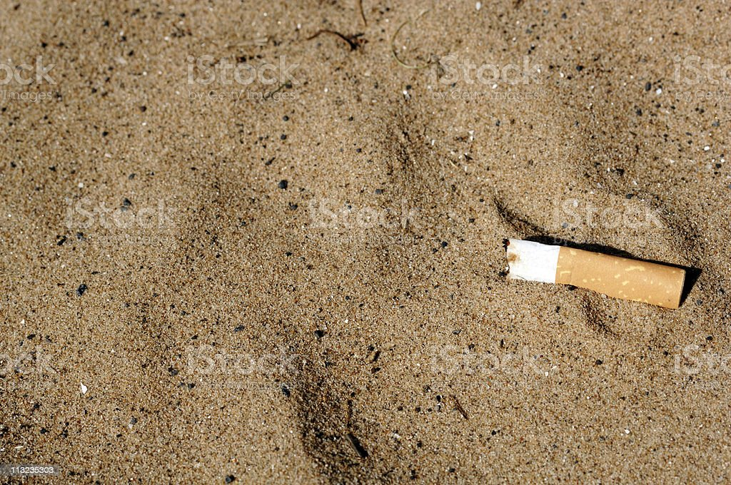 Litter on the beach, dumped cigarette butt royalty-free stock photo