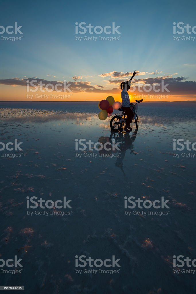 littl girl riding bicycle on the water with color balloons stock photo