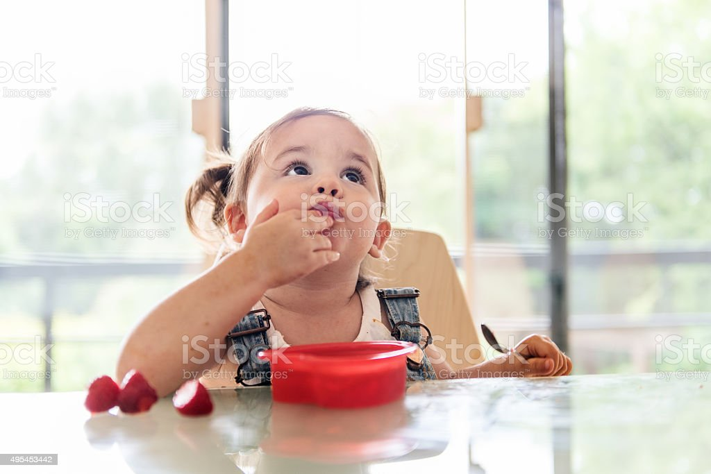 Little 2 years old girl eating jello stock photo