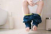 Little 7 years old boy on toilet.