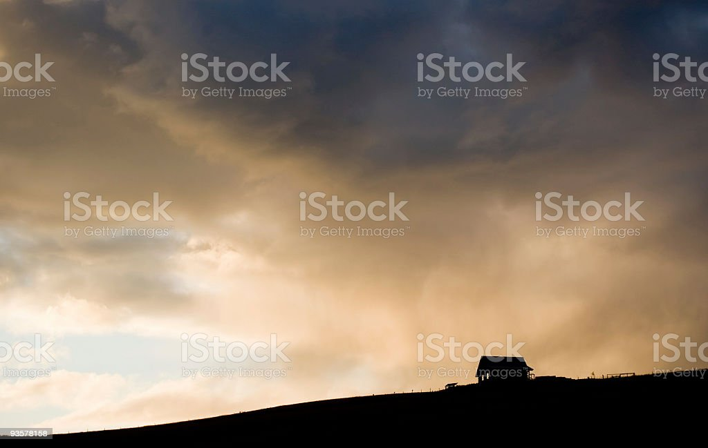 Little abandoned farmhouse, prairie hillside with dramatic summer storm stock photo