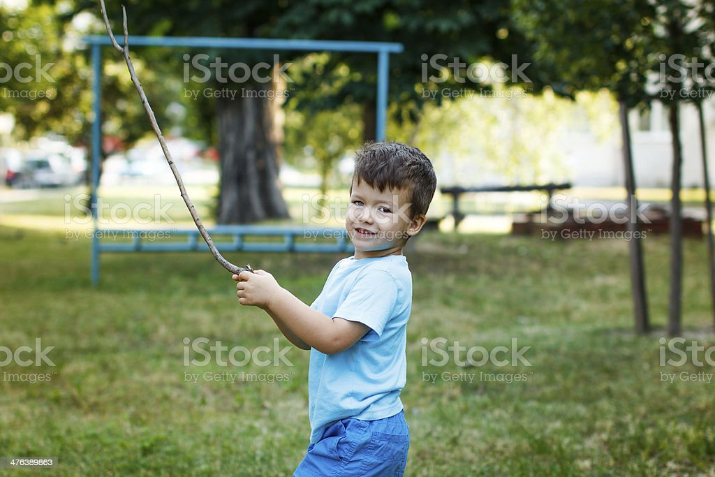 Little active boy with branch at park royalty-free stock photo