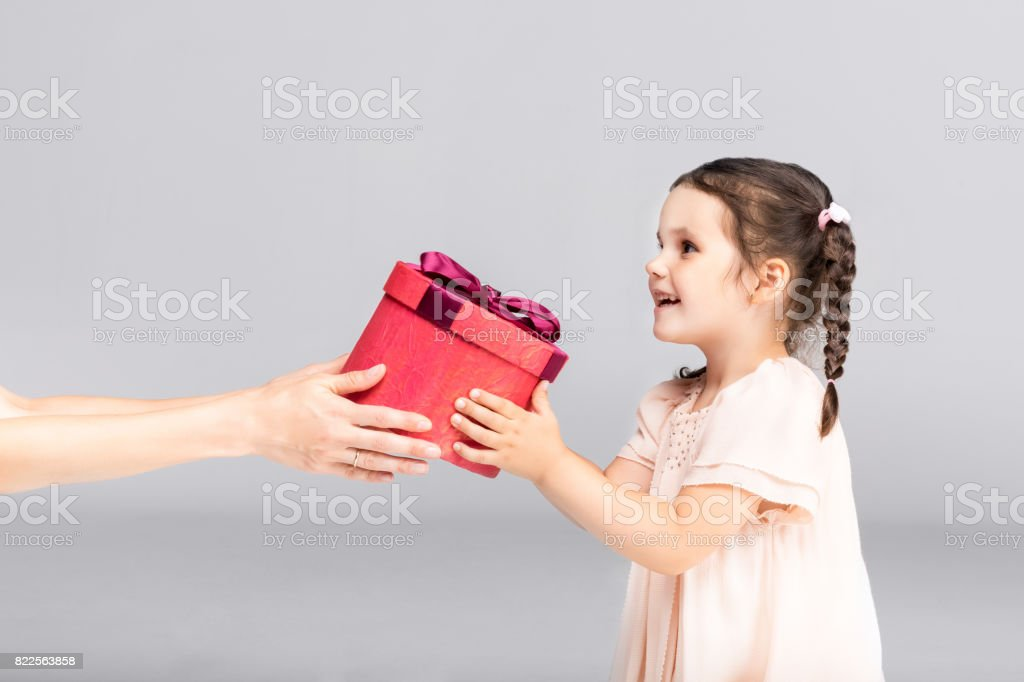 little adorable girl in beautiful dress taking a gift, isolated on grey stock photo