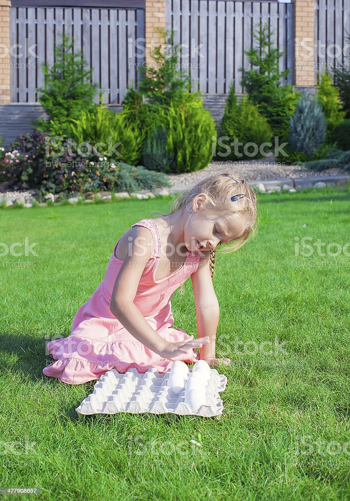 Little adorable girl playing with white Easter eggs stock photo