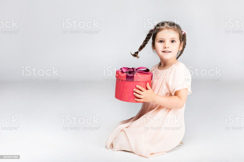 little adorable girl with braids holding red gift box, isolated on grey stock photo
