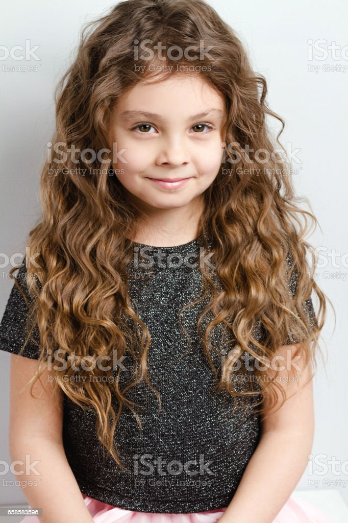 Little adorable girl with curly hair. stock photo