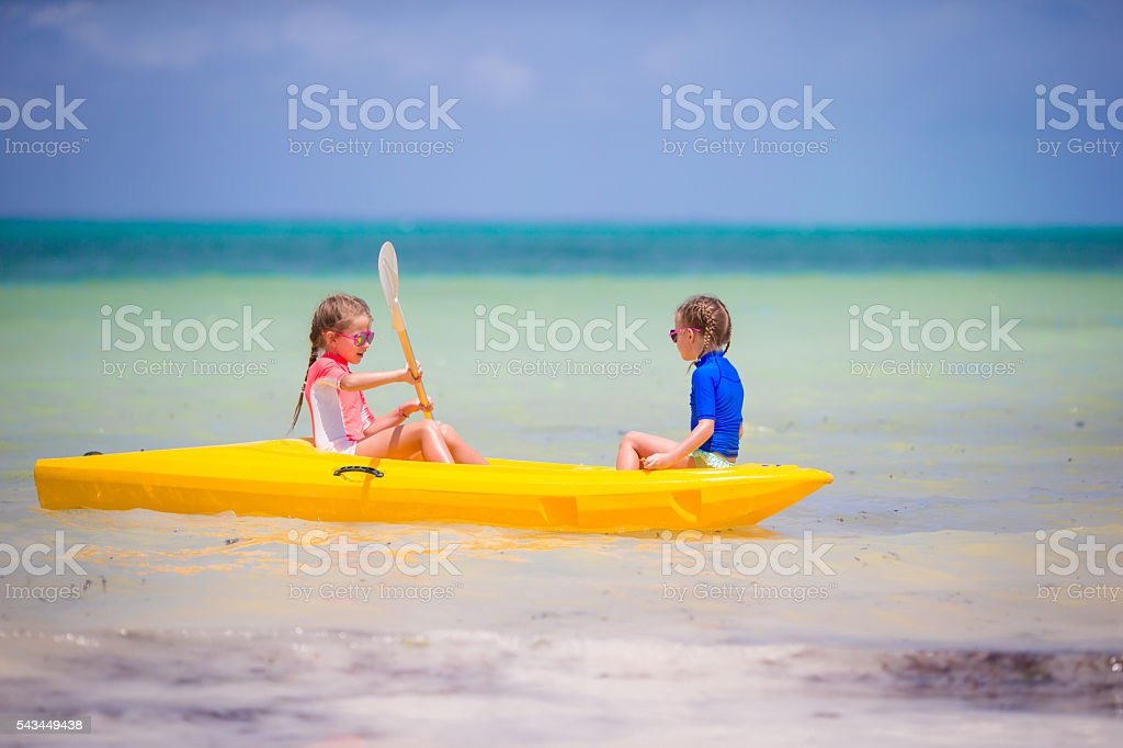 Little adorable girls enjoying kayaking in the sea stock photo