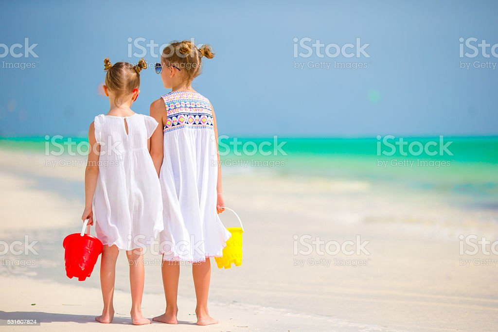 Little adorable girls with beach toys at tropical beach stock photo