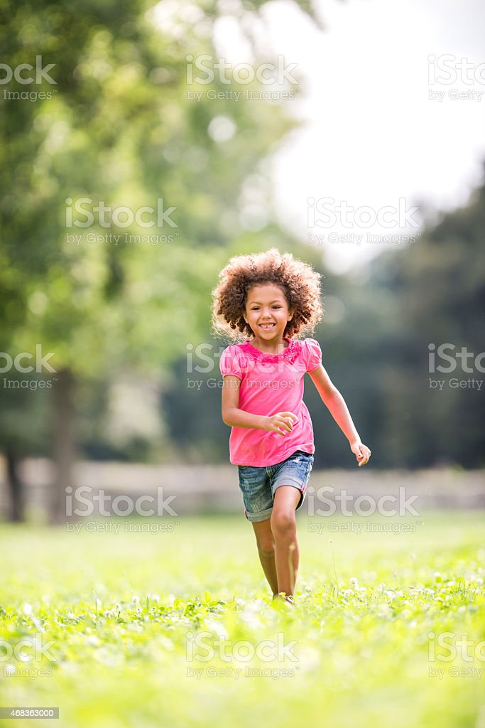 Little African American girl having fun while running outdoors. stock photo