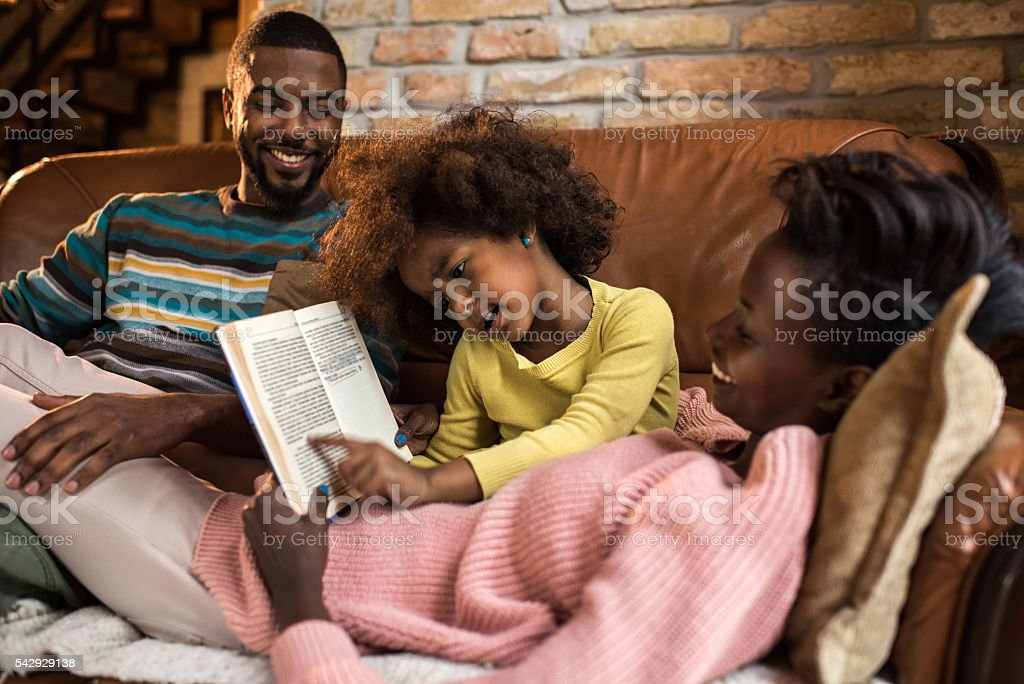 Little African American girl reading a book to her parents. stock photo