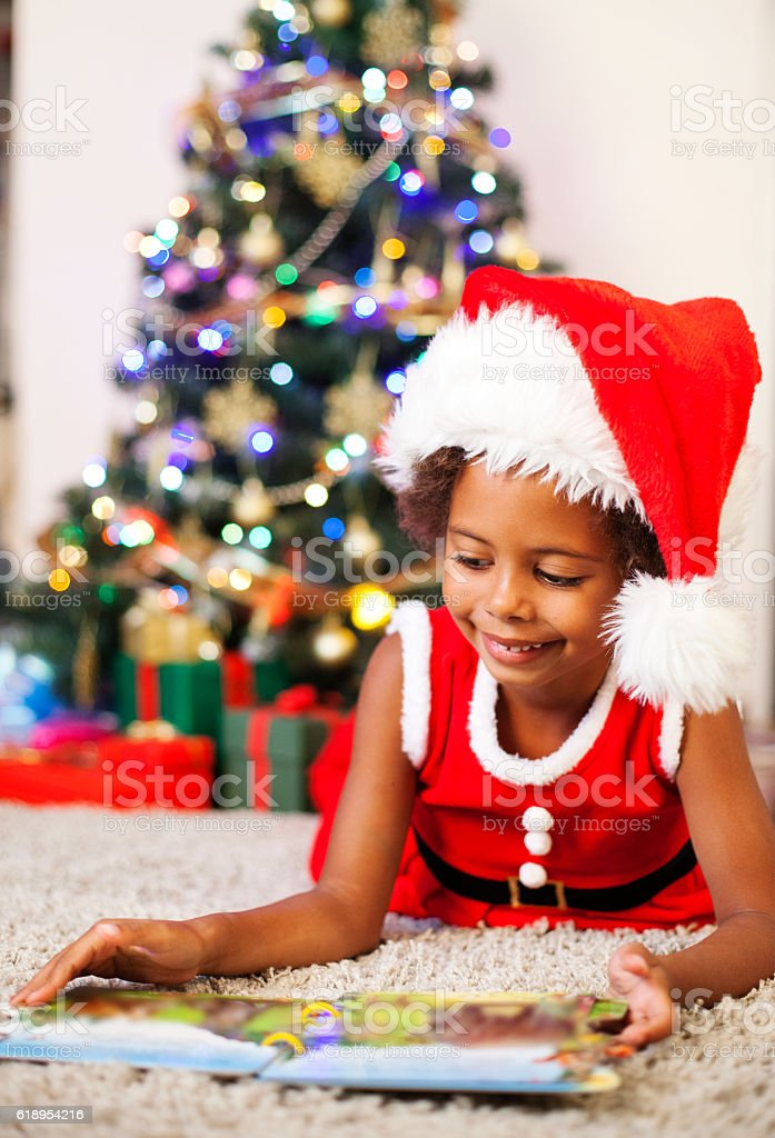 Little african american girl reading at Christmas tree stock photo