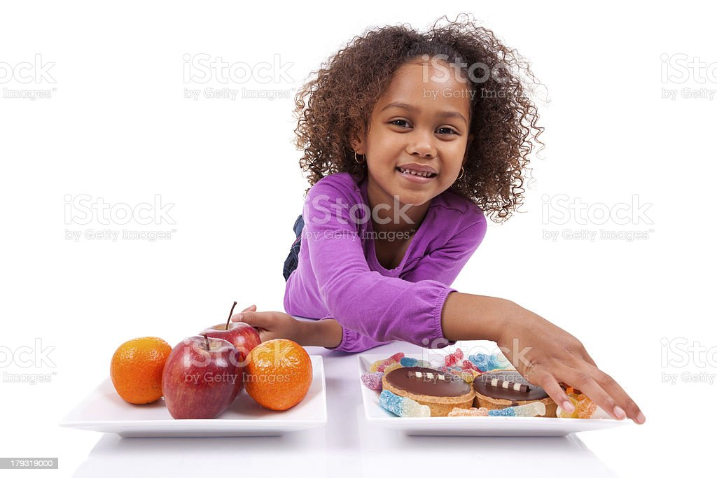 Little African Asian girl hesitating between fruits or  candy royalty-free stock photo