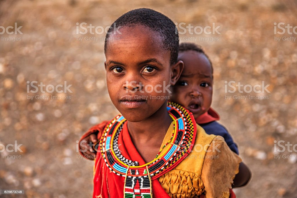 Little African girl carrying her baby brother, Kenya, East Africa stock photo
