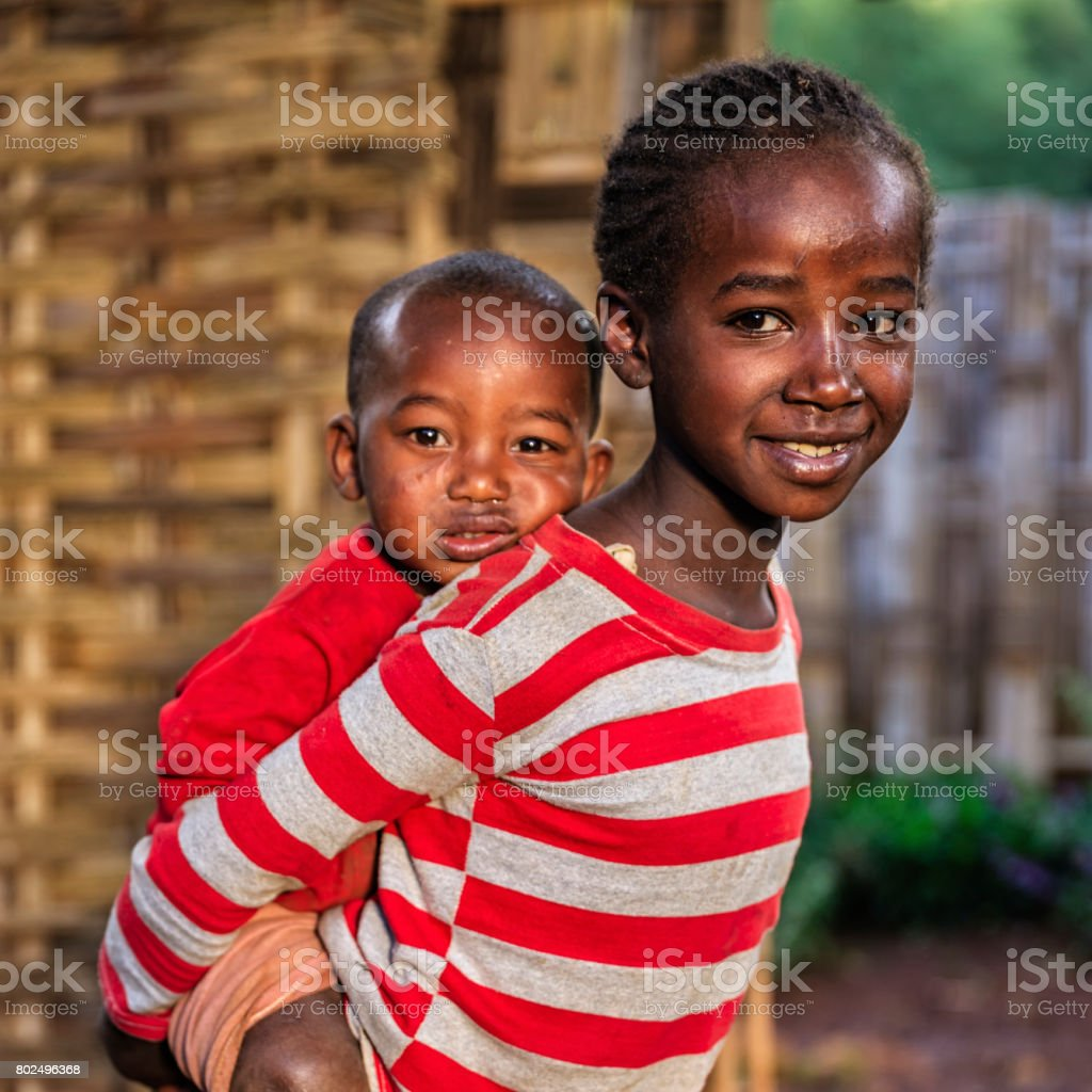 Little African girl carrying her brother on back, East Africa stock photo