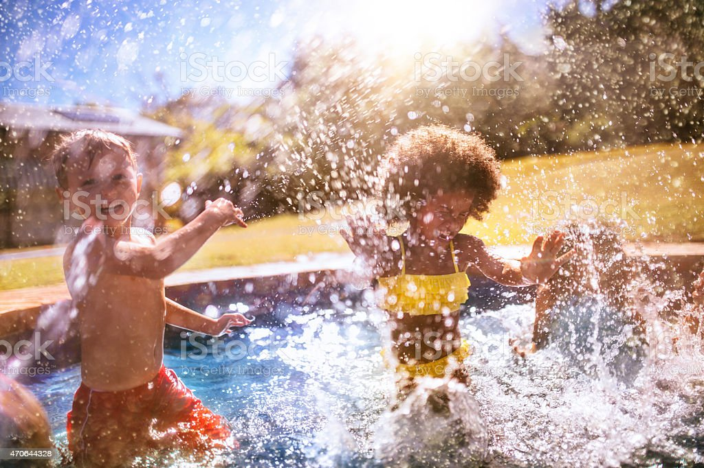 Little Afro girl and friend splashing water in swimming pool stock photo