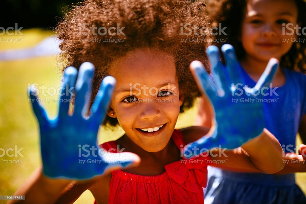 Little Afro girl showing hands full of blue paint stock photo