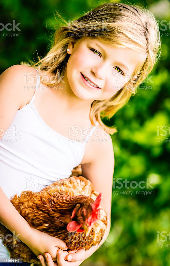 Little American Girl Holding Egg Laying Chicken royalty-free stock photo