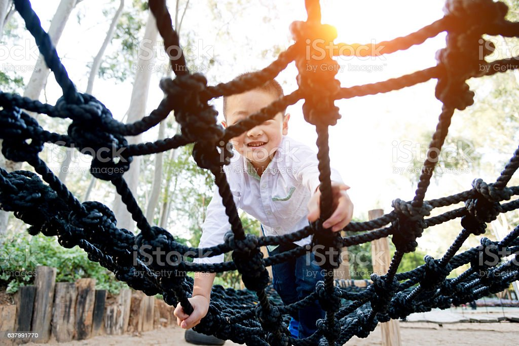 Little asian boy climbing rope frame stock photo