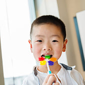 Little asian boy eating a colorful candy