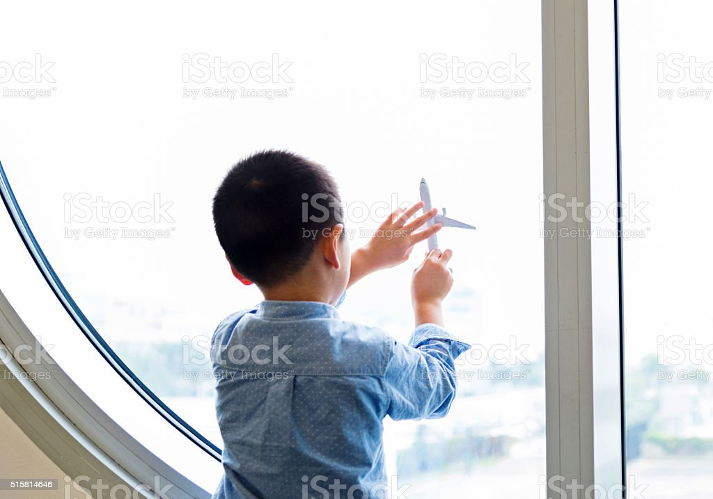 Little asian boy holding a toy plane in airport stock photo
