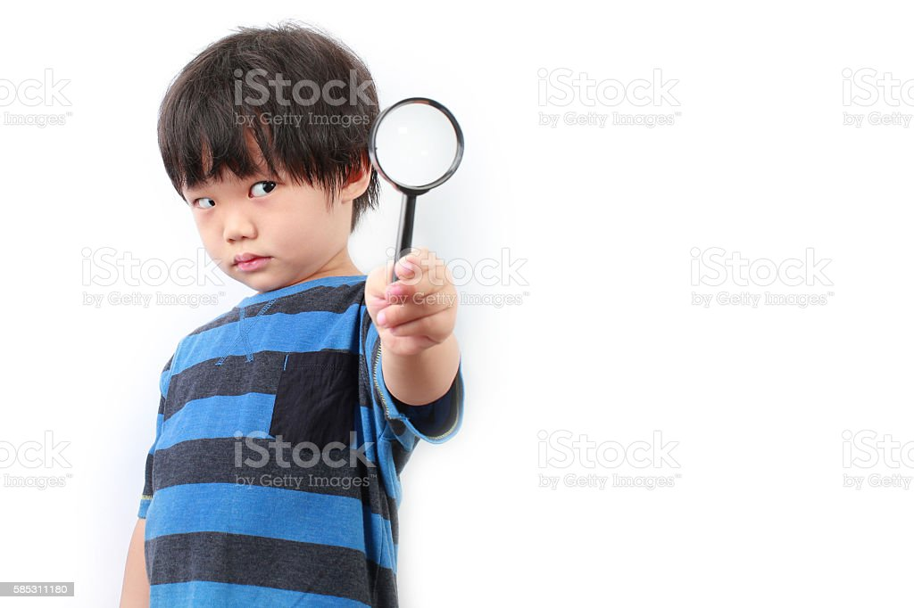 little Asian boy looking through a magnifying glass stock photo