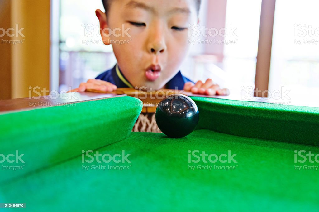 Little asian boy playing pool stock photo