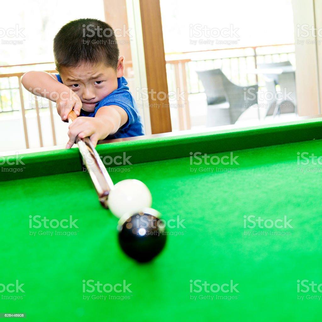 Little asian boy playing pool stock photo