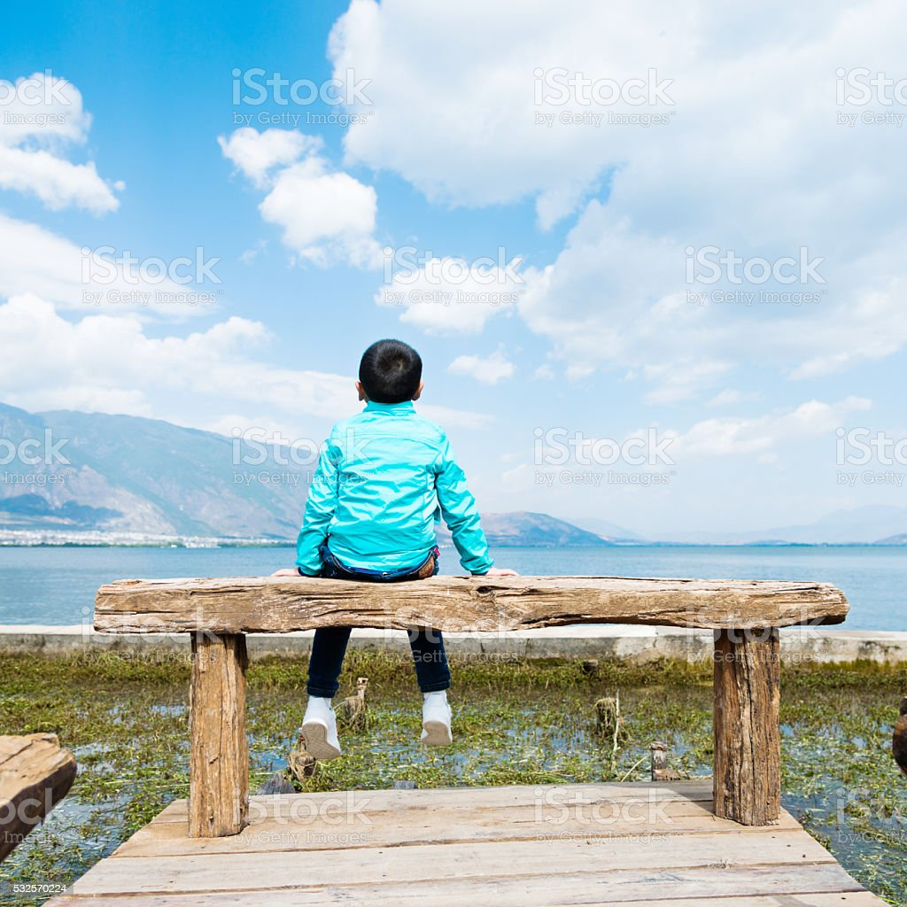 Little asian boy sitting on lakeside jetty stock photo