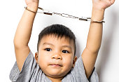 little Asian boy with handcuff on white background