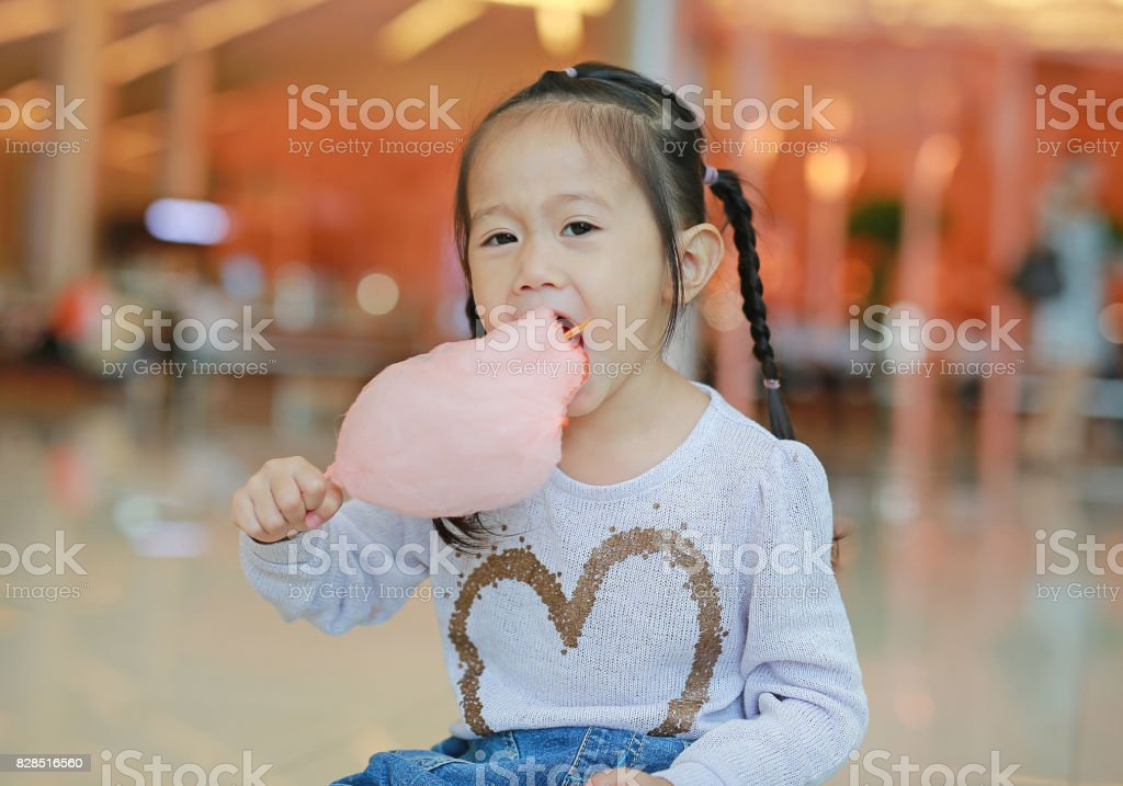 Little asian child girl eating sweet spongy candy. stock photo