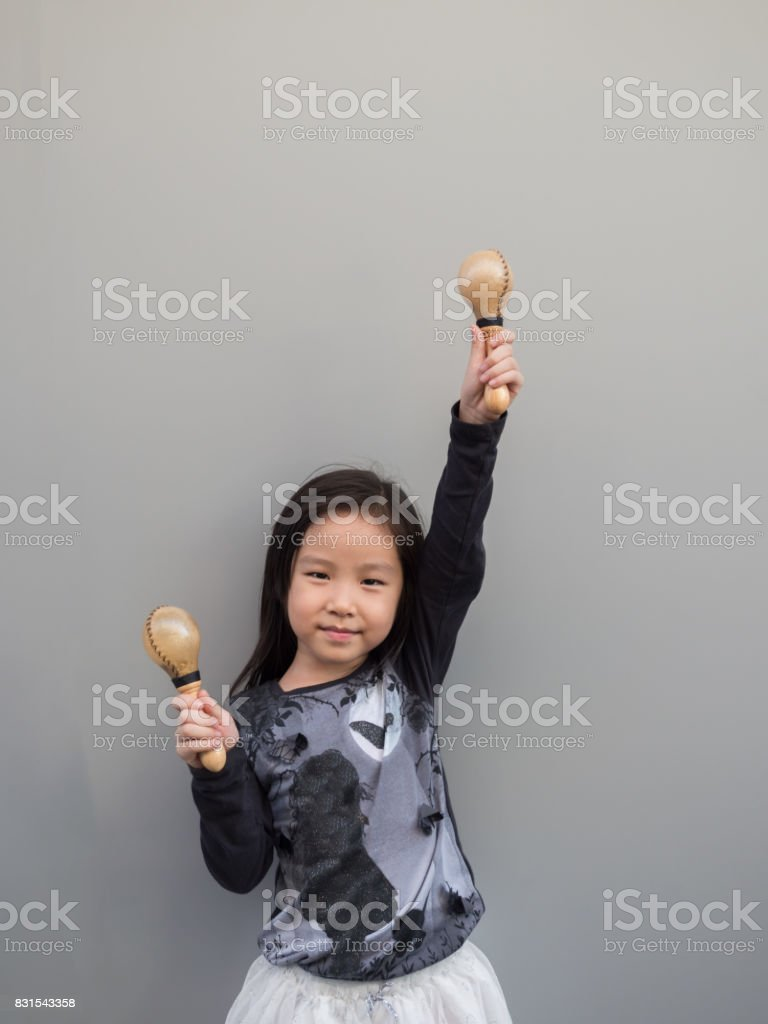 Little asian child play the maracas, gray background stock photo