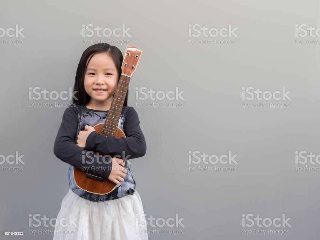 Little asian child play the ukulele, gray background stock photo