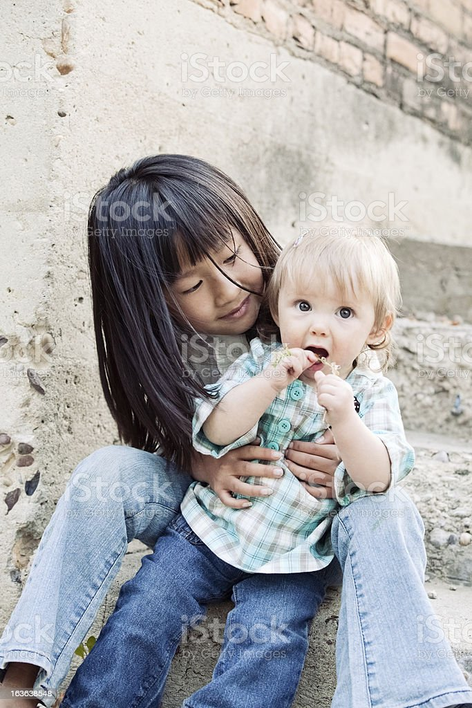 Little Asian Chinese Girl Together with Caucasian Blonde Baby royalty-free stock photo