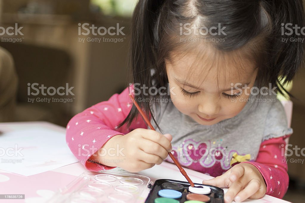 Little Asian girl learning to paint royalty-free stock photo